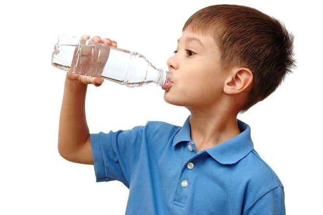 bé trai áo xanh uống nước