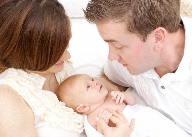 bố mẹ bế bé sơ sinh