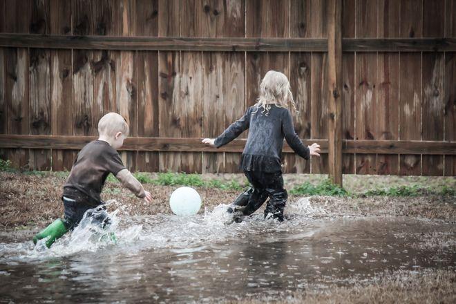 2 bé đá banh dưới mưa