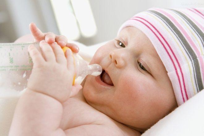 em bé cầm bình sữa bú