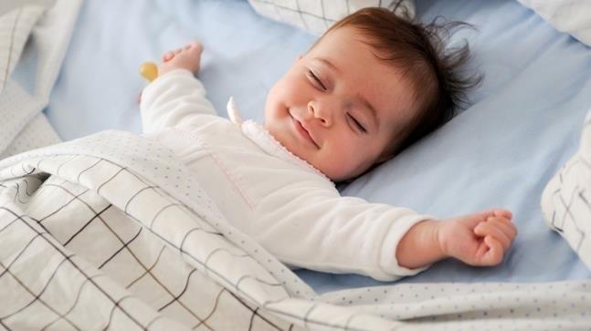 bé mỉm cười khi đang ngủ