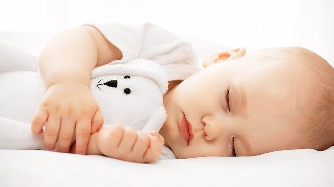 bé ôm gấu bông khi ngủ