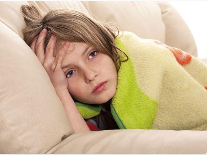 bé gái bị đau đầu nằm trên giường