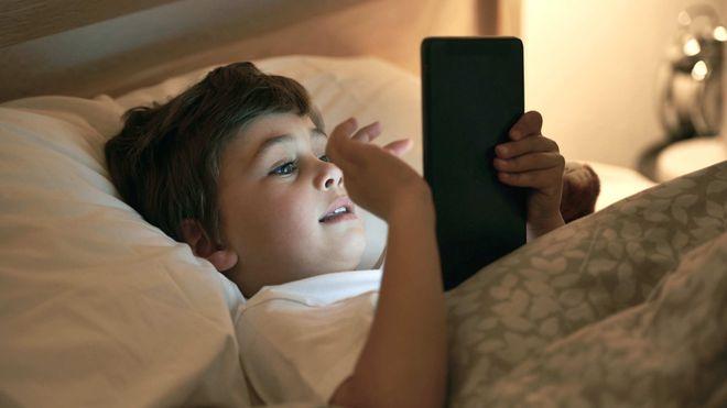 bé chơi ipad trên giường ngủ
