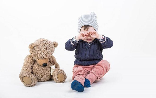 bé trai ngồi dụi mắt bên gấu bông