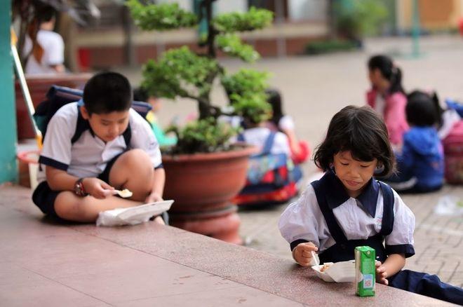 2 bé ngồi ăn ở hành lang trường