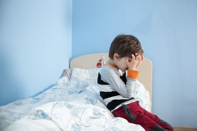 bé trai ôm đầu ngồi bên giường ngủ