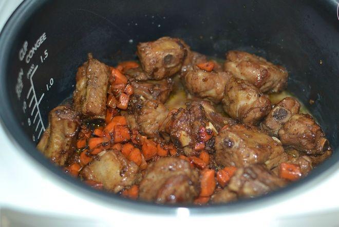 cho sườn, cà rốt và nấm hương vào nồi cơm điện nấu sôi