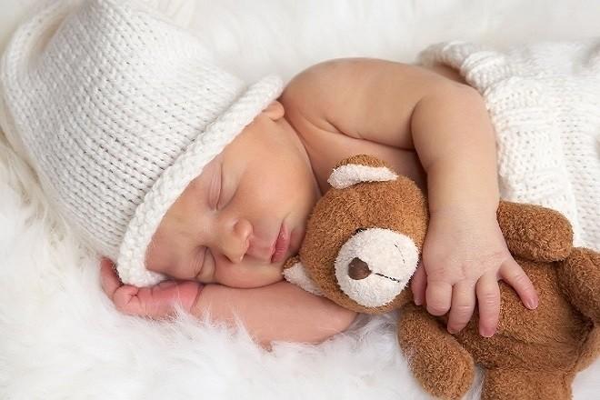trẻ sơ sinh ôm gấu ngủ ngon trong không gian rộng