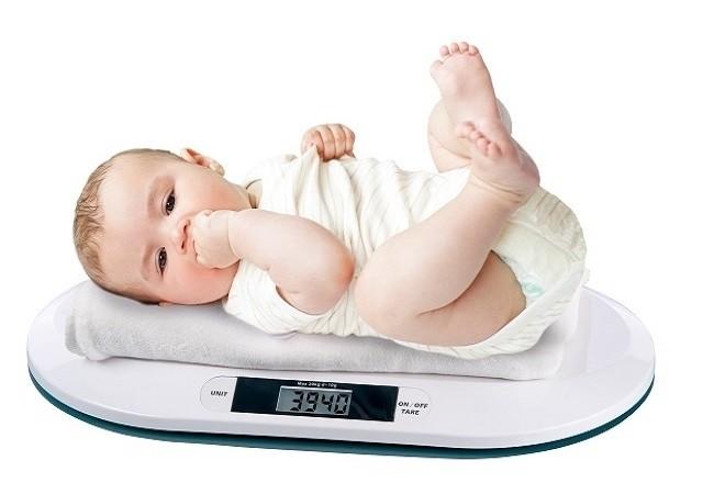trẻ 9 tháng tuổi nằm cân đối để đo chính xác cân nặng