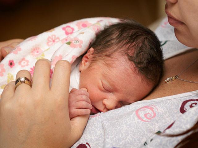 trẻ sinh non nằm trong vòng tay của mẹ