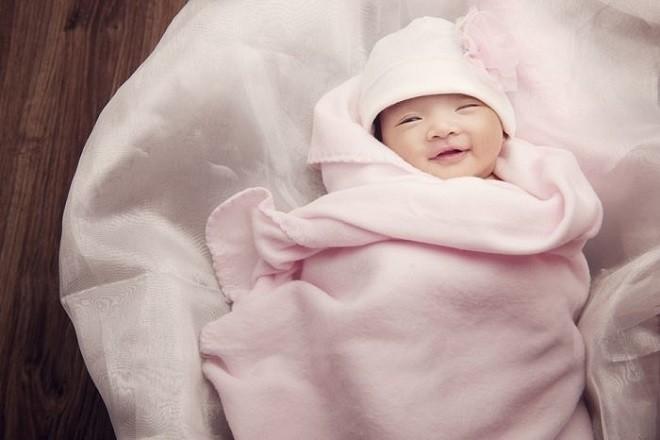 trẻ 2 tháng tuổi nằm cuộn trong chăn mỉm cười