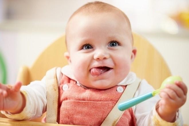 trẻ 9 tháng tuổi cầm nắm đồ dùng để ăn dặm