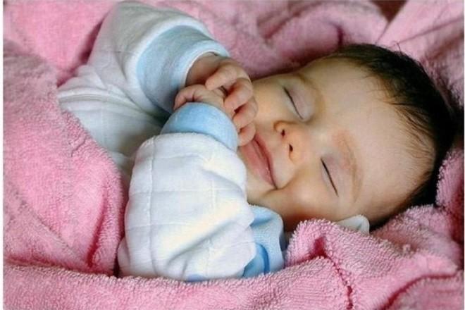 trẻ sơ sinh ngủ trong chăn mỉm cười