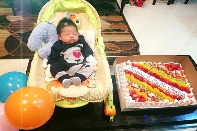 bé trai nằm trong ghế bên bánh đầy tháng