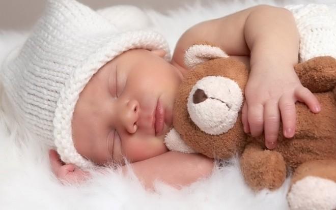 Bé ôm gấu bông ngủ say.