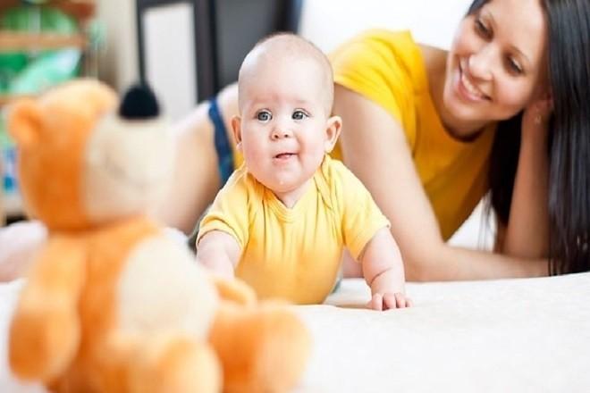 trẻ 4 tháng tuổi biết lật người dưới sự giám sát của mẹ