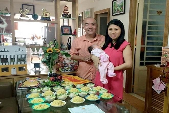 bố mẹ bồng bé trong lễ cúng đầy tháng