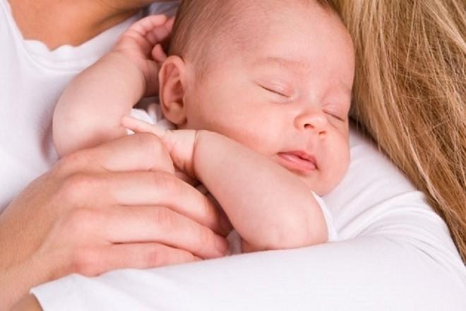 trẻ sơ sinh nằm ngủ trong tay mẹ