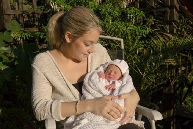 mẹ ẵm bé sơ sinh phơi nắng