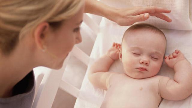 mẹ xoa đầu cho bé đang ngủ