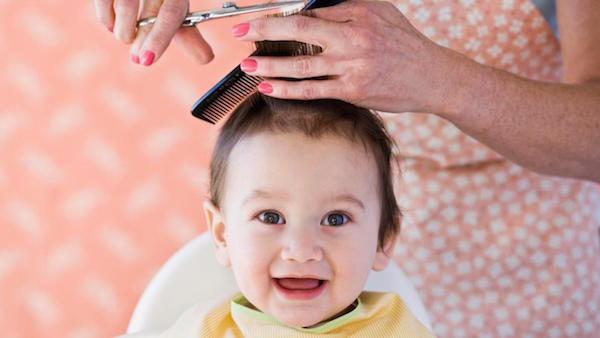 bé cười khi được cắt tóc