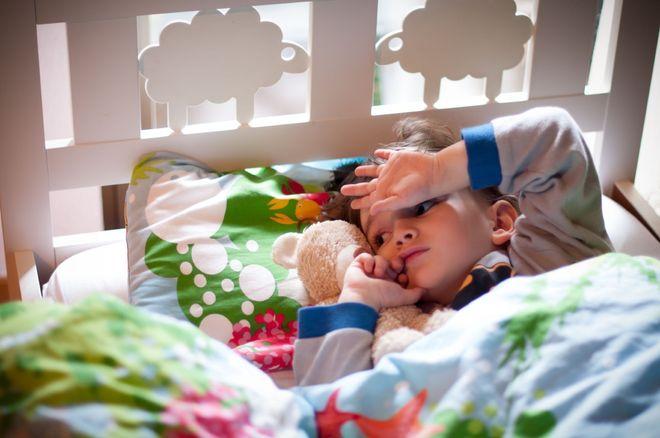 bé nằm gác tay lên trán không ngủ được
