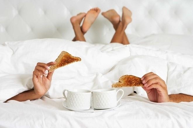 cặp đôi nằm trên giường ăn sáng