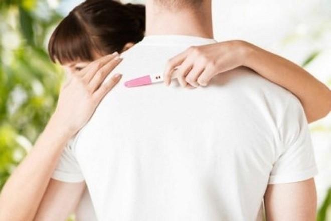 cô gái cầm que thử thai ôm chàng trai