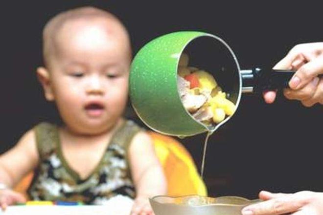bé nhìn mẹ chắt nước chảo đồ ăn