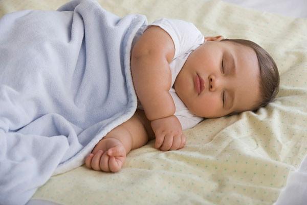 bé ngủ nằm nghiêng được đắp khăn