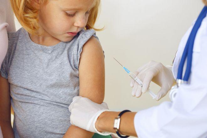 giữ tay bé gái tiêm vắc xin