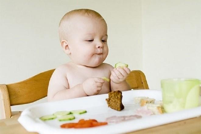 bé sơ sinh đang cầm thức ăn dặm