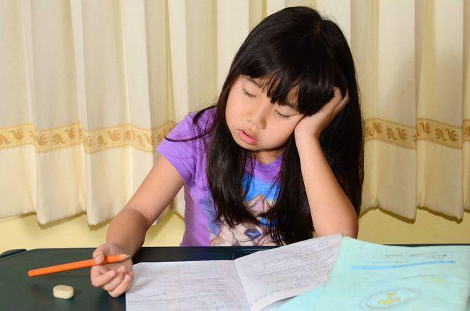 bé gái ngủ gật khi đang làm bài