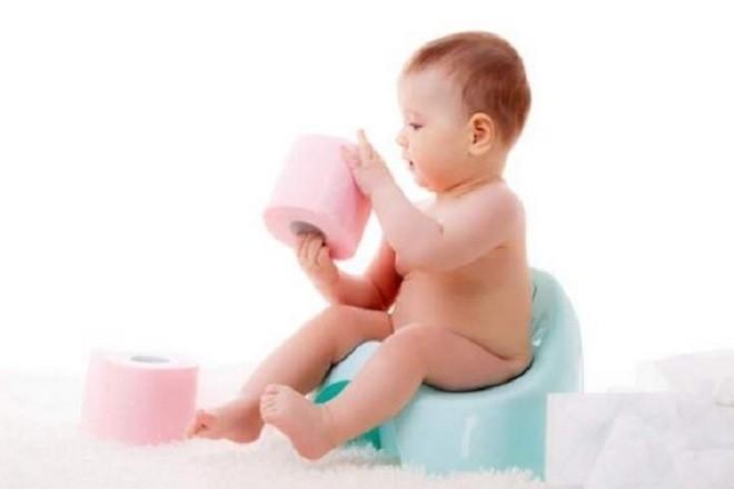 bé ngồi bô nghịch cuộn giấy