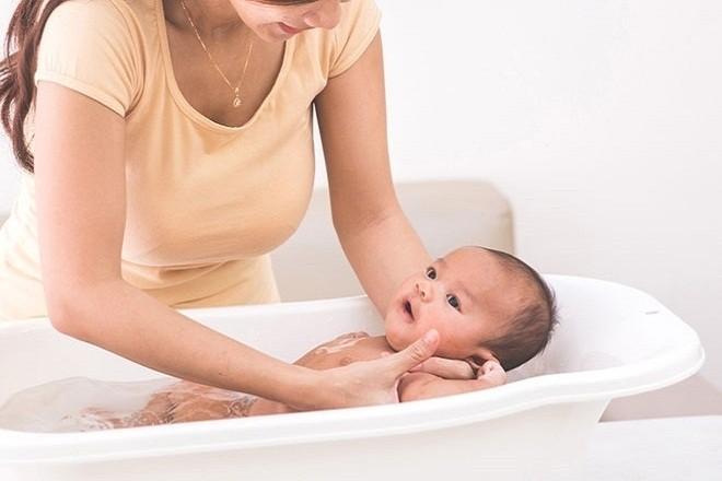 mẹ tắm nước ấm cho bé