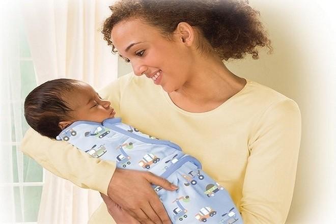 mẹ quấn khăn cho trẻ sơ sinh ngủ say