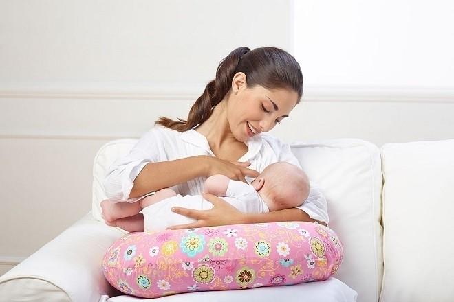 trẻ sơ sinh đang nằm bú sữa mẹ
