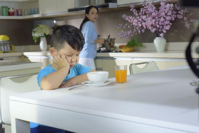 bé ngồi chống tay không chịu ăn