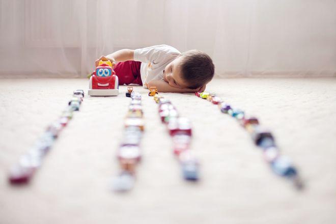 bé nằm trên sàn xếp 3 hàng xe đồ chơi