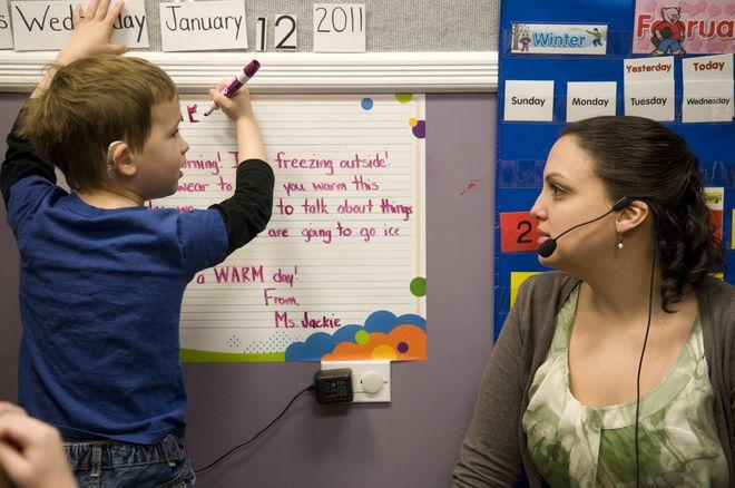 dạy bé trai viết chữ lên bảng