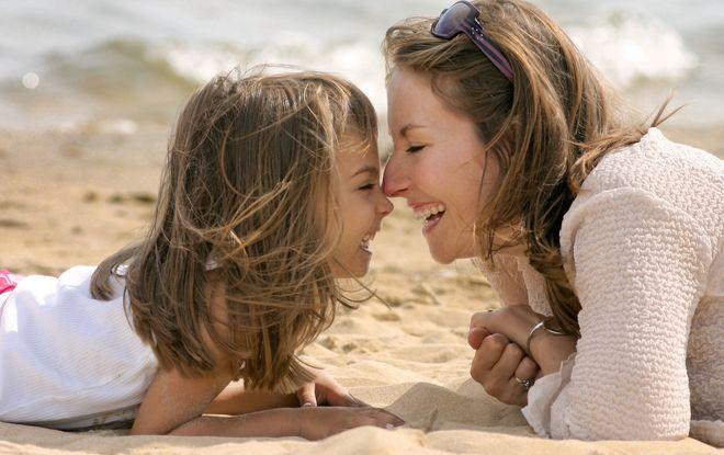 mẹ và con gái âu yếm nhau trên bãi biển