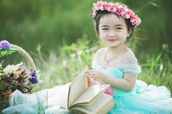 bé gái đầm xanh ngồi ôm sách với thiên nhiên