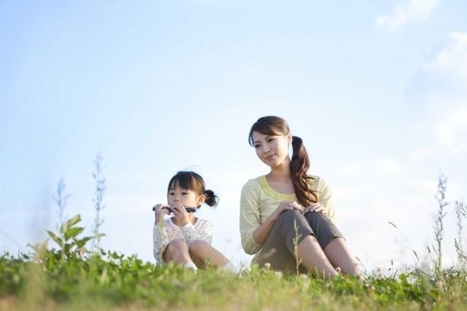 Mẹ ngồi cùng bé trên đồng cỏ