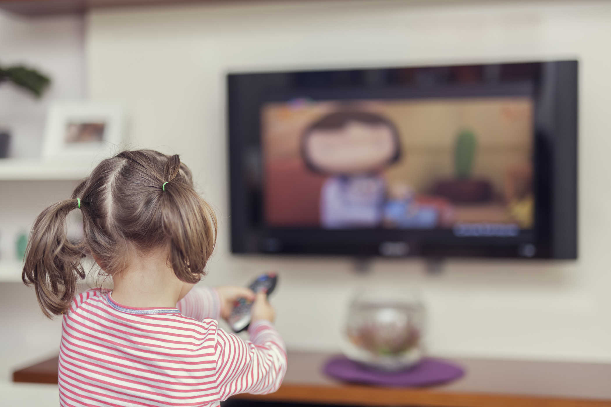 bé gái ngồi coi tivi
