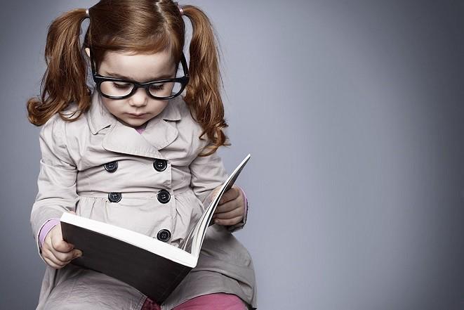 bé gái đeo kính đọc sách