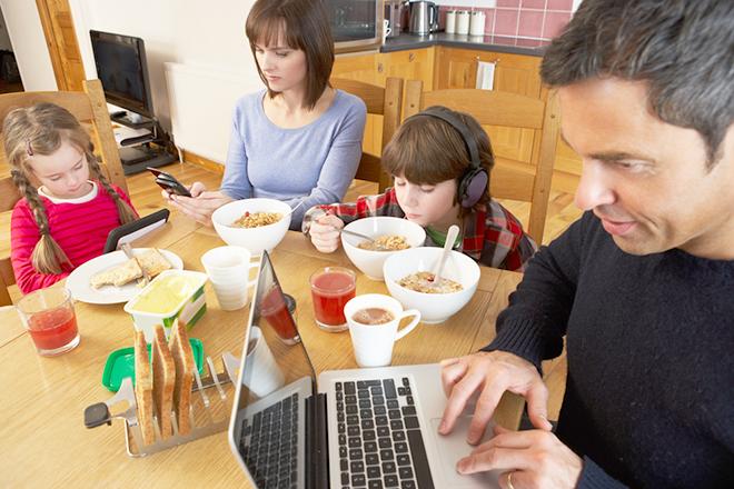 Gia đình vừa ăn vừa xem điện thoại máy tính