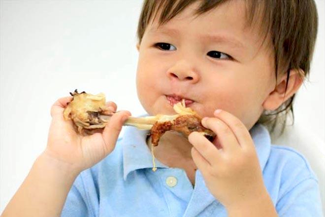 Trẻ ăn đùi gà