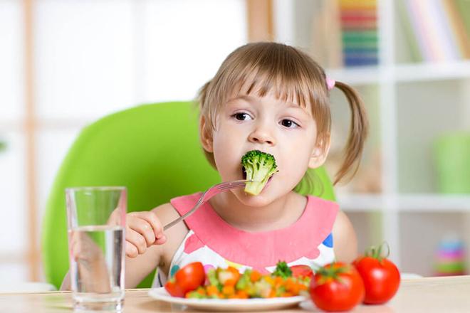 Bé 2 tuổi đang ăn rau