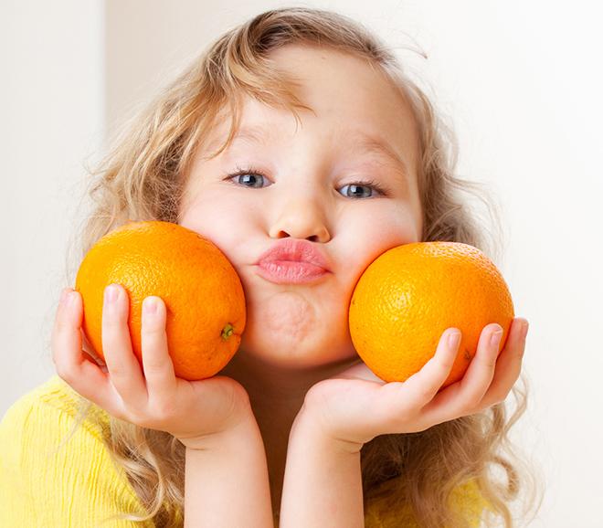 Trẻ cầm 2 trái cam